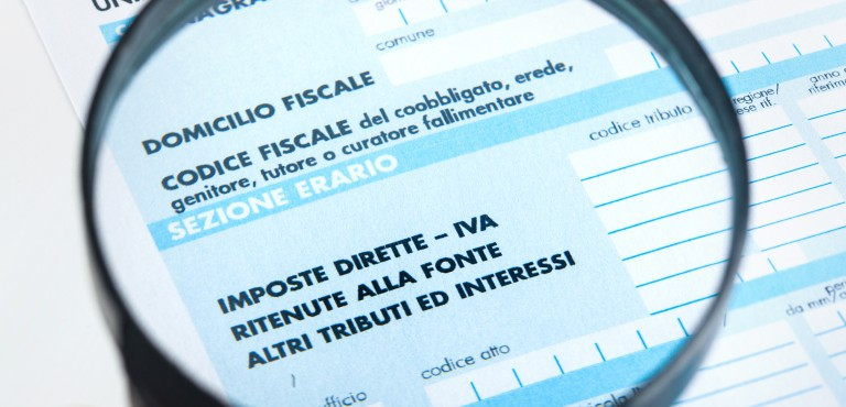 F24 for the tax return in Italy with magnifying glass.